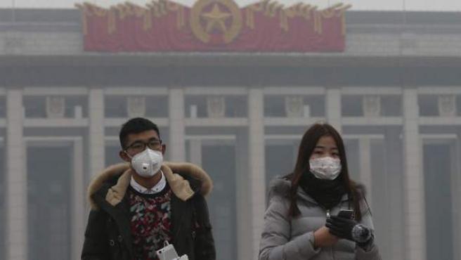 Una pareja usa mascarillas para protegerse de la contaminación ambiental durante una visita a la plaza de Tiananmen en Pekín (China).