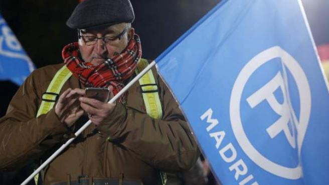 Un simpatizante del PP, en la calle Génova, durante la noche electoral del 20-D.