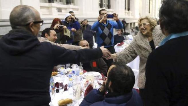 La alcaldesa de Madrid, Manuela Carmena (d), saluda a algunas de las 200 personas sin hogar que esta noche cenan en el Palacio de Cibeles, organizadas por la Fundación Mensajeros de la Paz que preside el padre Ángel en colaboración con el Ayuntamiento de Madrid.-