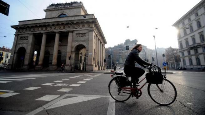 Una ciclista circula por las calles de Milán (Italia).