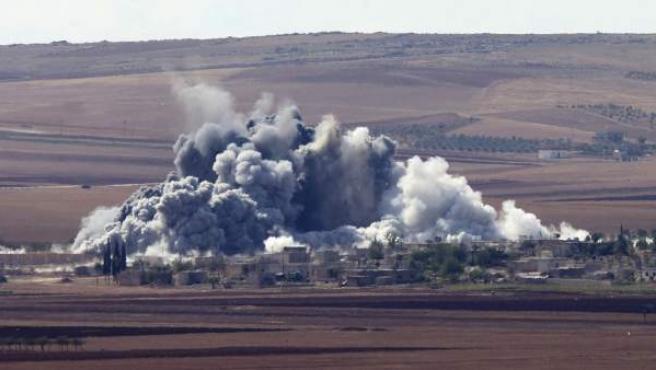 Columnas de humo gris se elevan sobre la población de Minaze tras un aparente bombardeo de las fuerzas de la coalición lideradas por EE UU contra el grupo radical Estado Islámico (EI), cerca de la localidad kurdo siria Kobani.