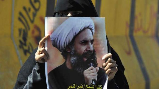 Imagen de archivo en la que una mujer sostiene una imagen del clérigo chií Al Nimr tras conocer su condena de pena de muerte.