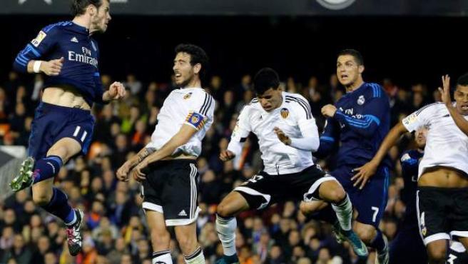 El delantero galés del Real Madrid Gareth Bale (i) cabecea para conseguir el segundo gol del equipo frente al Valencia CF.