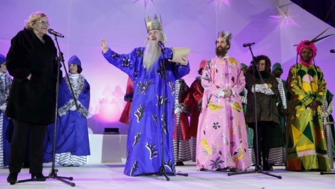 El rey Melchor (2i), acompañado de Gaspar (3d), y Baltasar (d), junto a la alcaldesa de Madrid, Manuela Carmena (i), y la concejala de Cultura, Celia Mayer (2d), durante su intervención en el escenario de la Plaza de Cibeles.