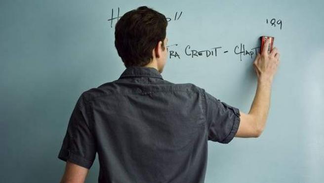 Un profesor escribe en una pizarra durante una clase.