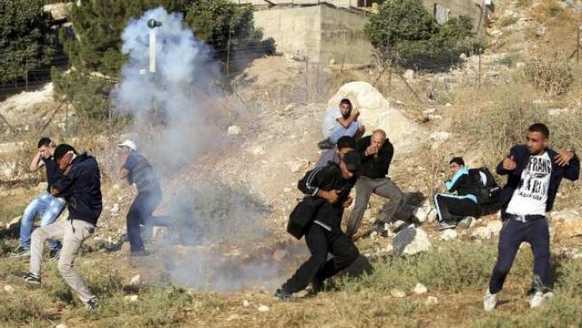 Un grupo de palestinos huye del gas lacrimógeno arrojado por la policía tras intentar cruzar la valla fronteriza cerca del punto de control de Kalandia en Al Ram (Cisjordania). Hoy se celebra el cuatro rezo del viernes del mes musulmán sagrado de ramadán y en Cisjordania muchos musulmanes cruzan la frontera para asistir a las mezquitas.