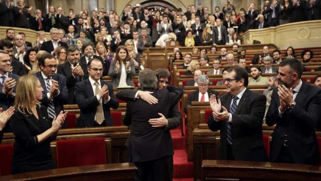 El presidente catalán en funciones, Artur Mas (de espaldas), saluda a Carles Puigdemont, poco antes de comenzar el pleno del Parlament en el que se ha debatido la investidura de Puigdemont.