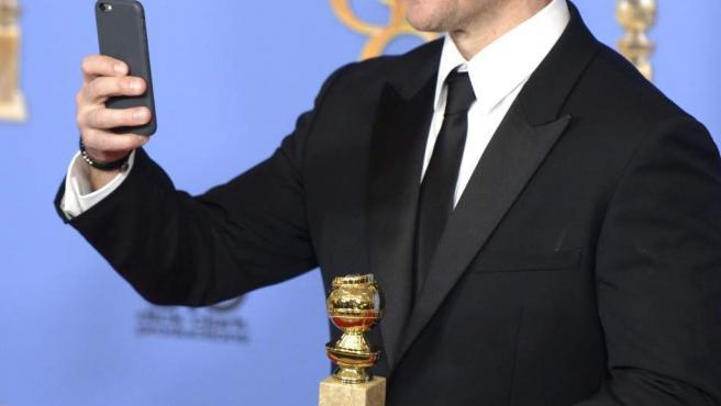 El actor estadounidense Matt Damon con el premio al Mejor Actor de Comedia por The Martian hace fotos con su móvil durante la 73 edición de los Globos de Oro en Beverly Hills, California, EE UU.
