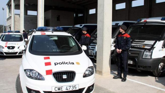 Agentes de los Mossos d'Esquadra junto a varios vehículos policiales.