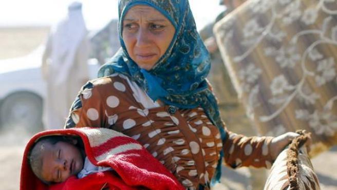 Una mujer sostienen a un bebé tras cruzar la alambrada en la frontera entre Siria y Turquía cerca de Sanliurfa.