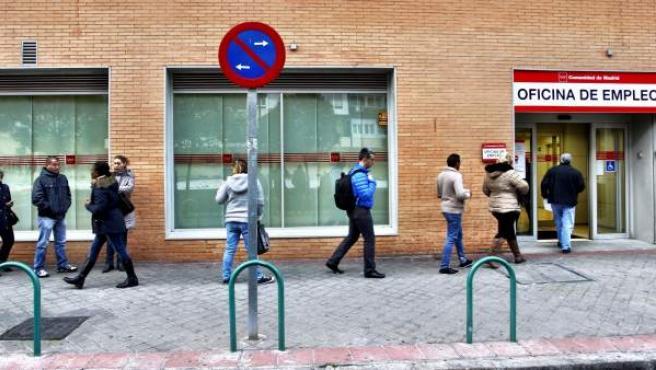 Varias personas hacen cola en una oficina de empleo.