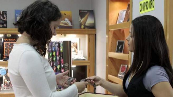 Una clienta conversa con la dependienta de una tienda.