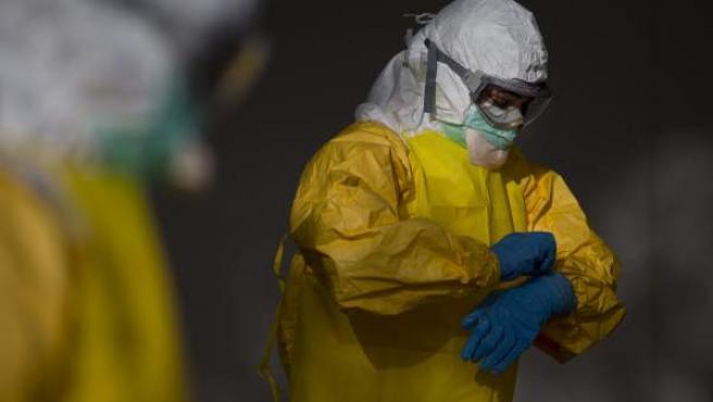 Un sanitario se coloca el traje protector contra el ébola.