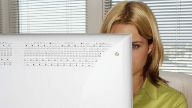 Una joven navega en Internet con un ordenador personal.