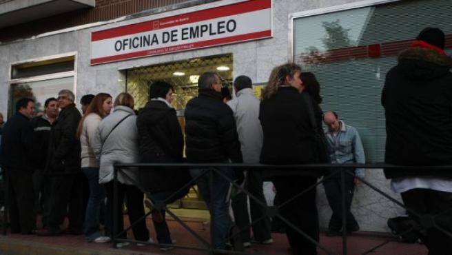 Varias personas hacen cola en una oficina del paro antes de la hora de apertura.