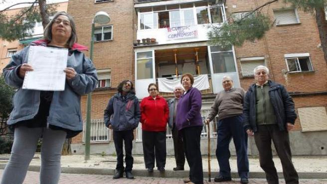 Un grupo de vecinos del número 53 de la calle Villalobos posa frente a su bloque, que tiene la fachada aún pendiente de rehabilitar.