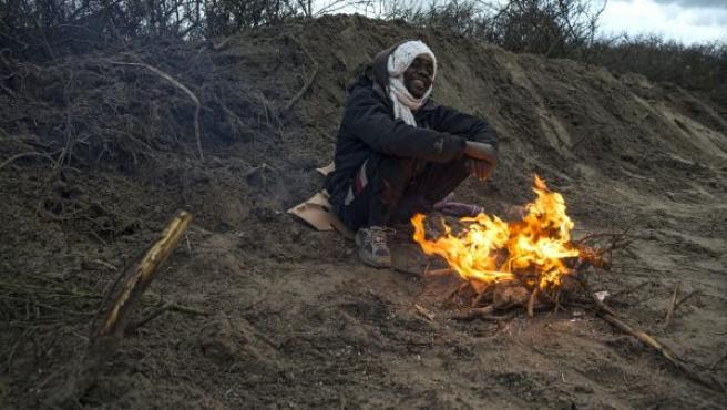 Un refugiado subsahariano se calienta al lado de una fogata en el campamento conocido como La Jungla, en Calais (Francia). Entre 4.000 y 7.000 migrantes viven en este asentamiento en condiciones de extrema precariedad.