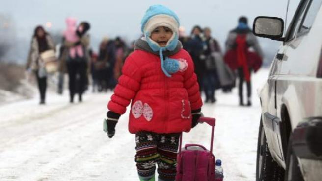 Refugiados sirios, iraquíes y afganos caminan por un camino nevado desde Macedonia a un campamento de recepción temporal de migrantes en Miratovac en la frontera entre Serbia y Macedonia.