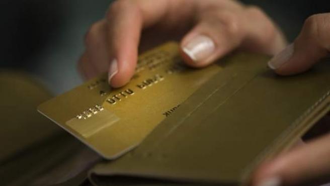 Una mujer saca de la cartera su tarjeta de crédito.