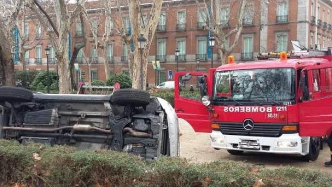 Los bomberos estabilizan el vehículo del accidente sucedido en el Paseo del Prado