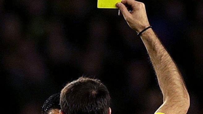 Un colegiado le muestra una cartulina amarilla a un jugador durante un partido de fútbol en marzo de 2015.