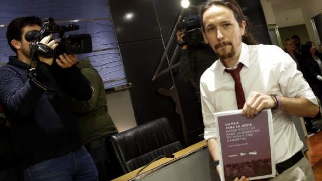 Pablo Iglesias posa en el Congreso con el documento que contiene las propuestas de Podemos para las negociaciones sobre la formación de Gobierno.