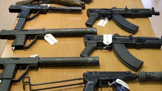 Varias armas encima de una mesa.