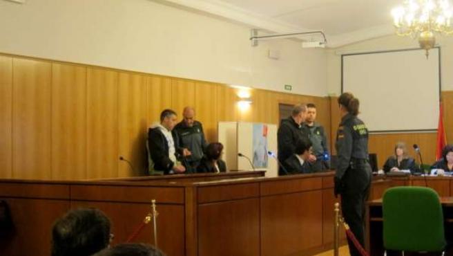 Los acusados, junto a agentes de la Guardia Civil, al inicio del juicio.