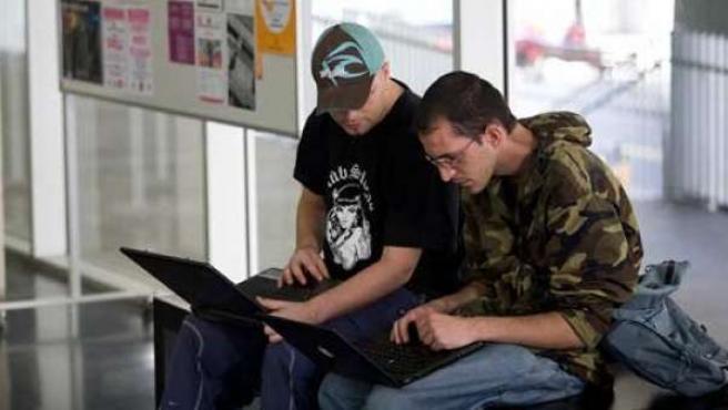 Dos jóvenes se conectan a Internet en un recinto con WiFi.