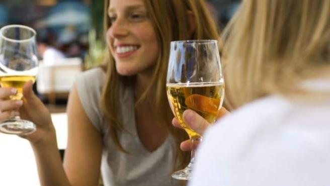 Dos jóvenes, sentadas en una terraza tomando una cerveza.
