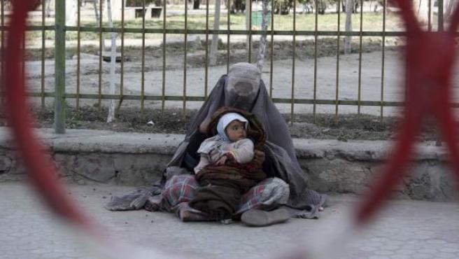 Una mujer afgana pide dinero con un bebé en brazos, en una calle de Kabul, Afganistán, en el Día Internacional de Mujer.