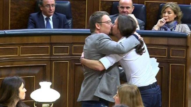 El líder de Podemos, Pablo Iglesias, y el de En Comú Podem, Xavier Doménech, celebrando su estreno en la tribuna de oradores de la Cámara Baja con un efusivo abrazo y un beso en los labios.