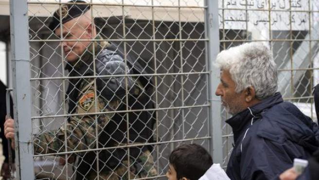 Un policía macedonio cierra el acceso fronterizo delante de un grupo de refugiados.