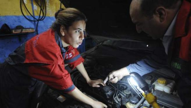 Una mujer, trabajando en un taller mecánico.
