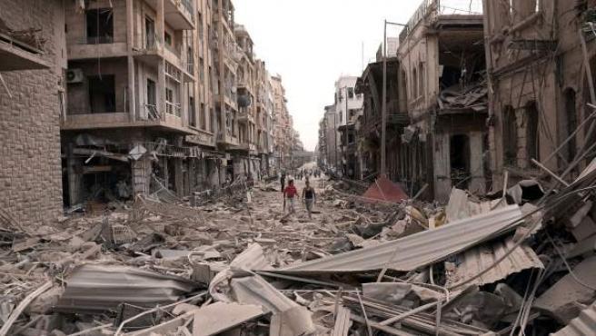 Ciudadanos sirios caminan entre escombros en la ciudad de Alepo, una de las más castigadas por la guerra siria.