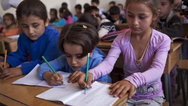 Niños sirios durante una clase de primaria en un colegio del distrito de Saif Al-Dawla, en Alepo (Siria). El Fondo de las Naciones Unidas para la Infancia (Unicef) ha instado a aumentar los esfuerzos para que la ayuda humanitaria llegue a los cientos de miles de niños atrapados por el conflicto.