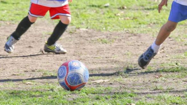 Adolescentes jugando al fútbol en una foto de archivo