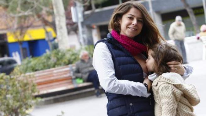 Marietta Herencias, de 33 años, con su hija tomando teta, en una plaza pública, en Madrid.