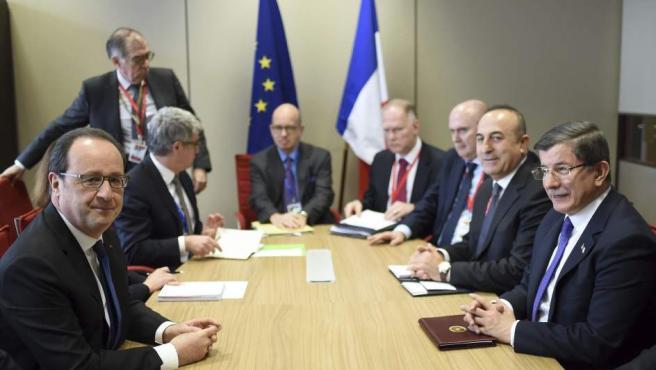 El presidente francés François Hollande (izda) y el primer ministro turco Ahmet Davutoglu (dcha), durante la reunión mantenida en el marco de la cumbre de los jefes de Estado y de Gobierno de la Unión Europea (UE), en Bruselas, Bélgica