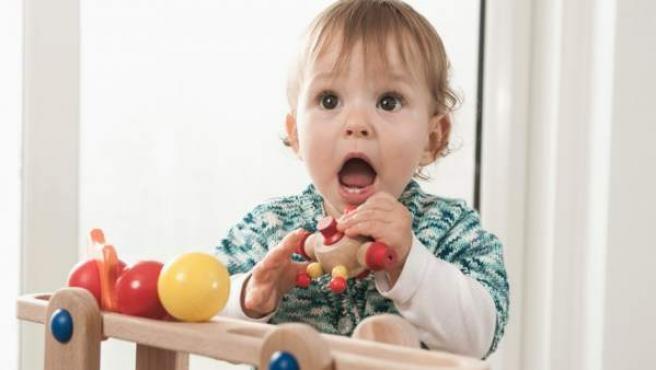 Una bebé de un año se lleva a la boca un juguete de madera mientras juega en casa.