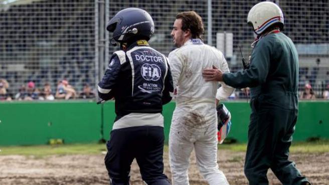 Alonso, acompañado por operarios del circuito de Albert Park tras su accidente.