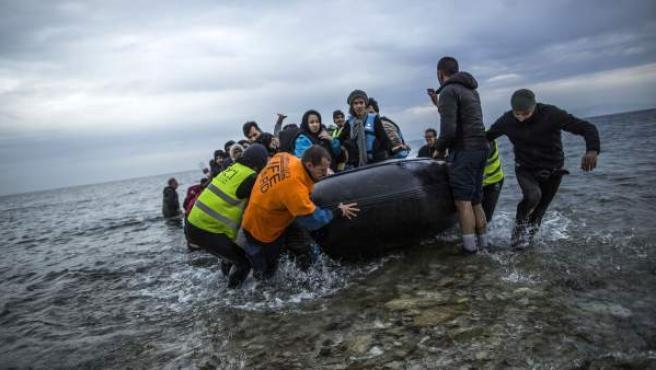 Migrantes y refugiados llegan en una embarcación a la isla griega de Lesbos.