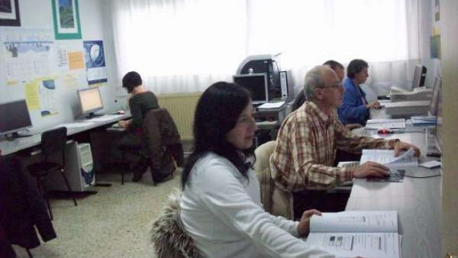 Personas adultas estudiando con ordenadores