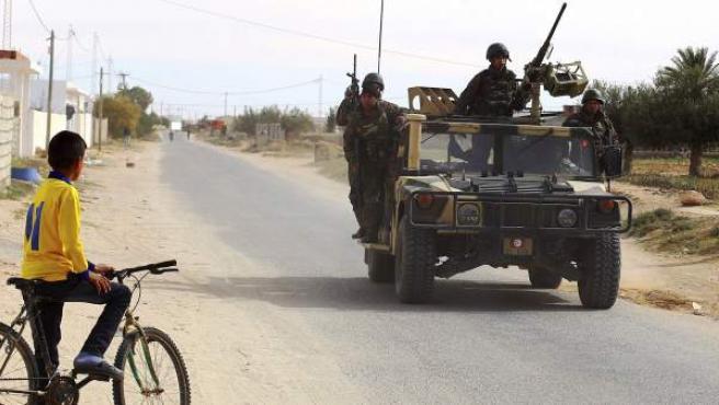 Un niño observa a soldados patrullando cerca de la frontera con Libia en Ben Gardane, Túnez
