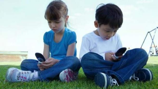 Dos niños usan un teléfono móvil.