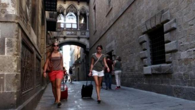 Dos turistas arrastran sus maletas en pleno barrio Gótico de Barcelona.