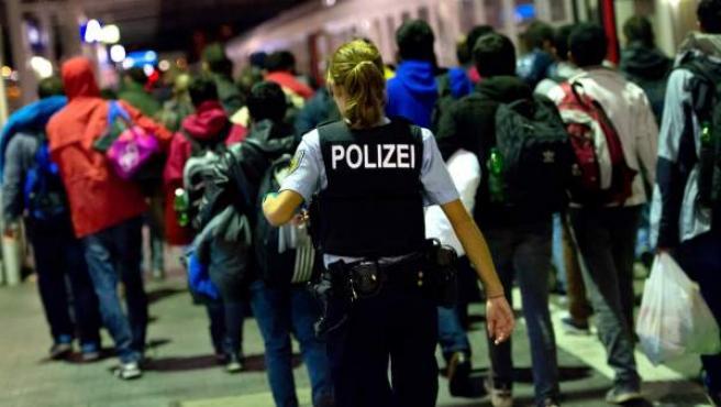 Una policía vigila a refugiados sirios al subir a un tren de Múnich a Dortmund.