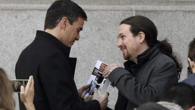 """El líder de Podemos, Pablo Iglesias (d), obsequia al secretario general del PSOE, Pedro Sánchez, con el libro """"Historia del Baloncesto de España"""", de Carlos Jiménez Poyato."""