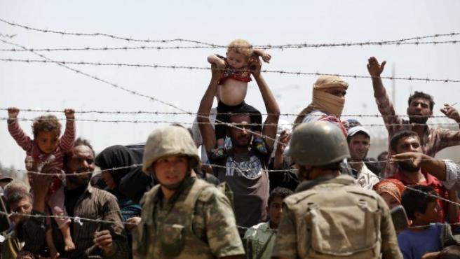 Fotografía tomada desde el paso fronterizo de Akçale, en la provincia de Sanliurfa, Turquía, en la que se muestra a varios refugiados sirios esperando para cruzar desde el lado sirio de la frontera.