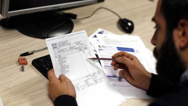 Un hombre revisa una factura comercial para comprobar los conceptos abonados.